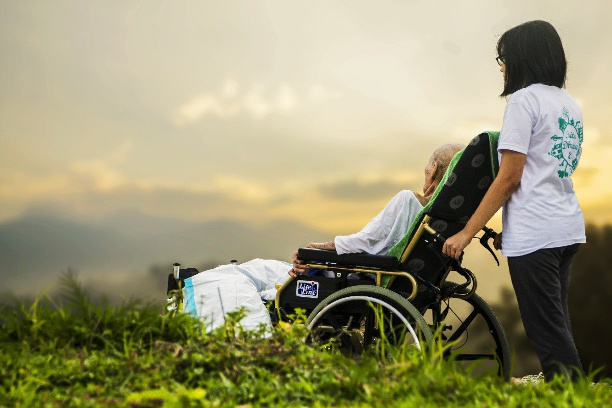 Anciano en silla de ruedas con cuidadora mirando el horizonte.