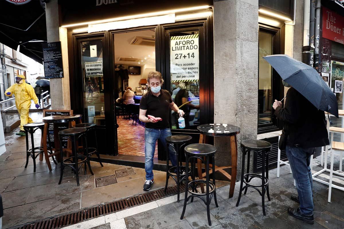 Un camarero se dispone a desinfectar el mobiliario del bar en Navarra.