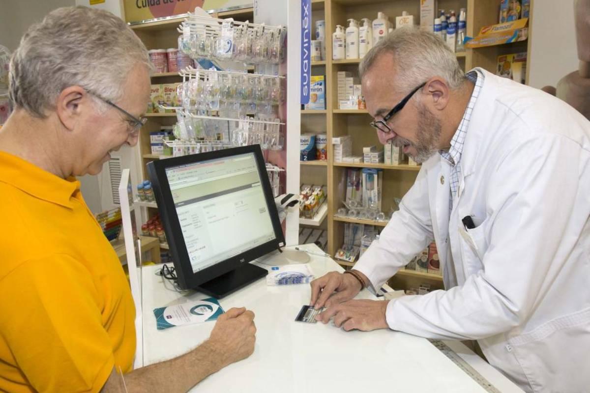 Manuel Ojeda, vicepresidente del COF de Sevilla, atendiendo en su farmacia (ya traspasada), en 2013.