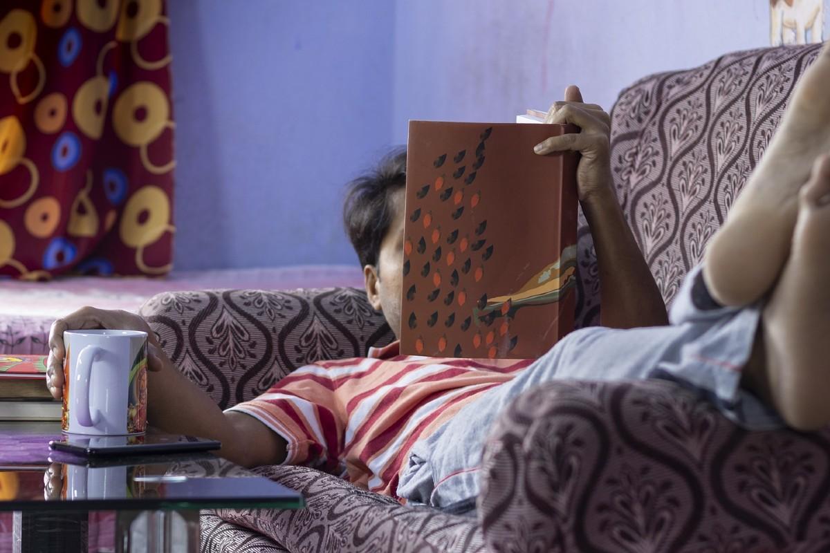 Varón tumbado en un sillón y leyendo un libro.
