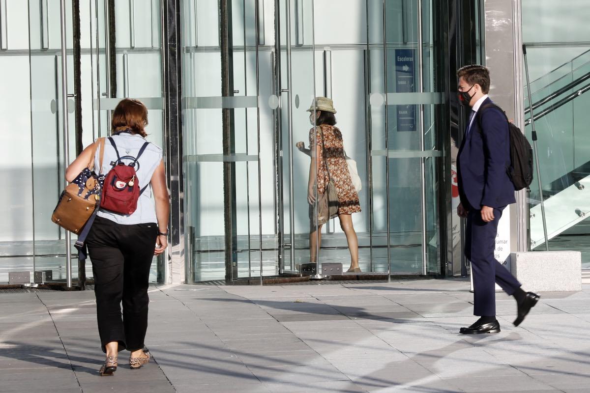 Varias personas llegan a su puesto de trabajo en un edificio de oficinas de Madrid (Fotografía: Javi Martínez).