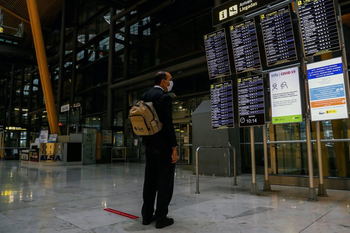 Un hombre observa el panel informativo con las próximas llegadas en el aeropuerto de Barajas en Madrid.