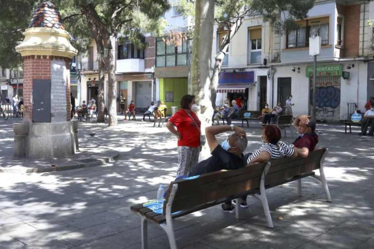 Personas en un banco de una plaza de Hospitalet de Llobregat, en Barcelona.
