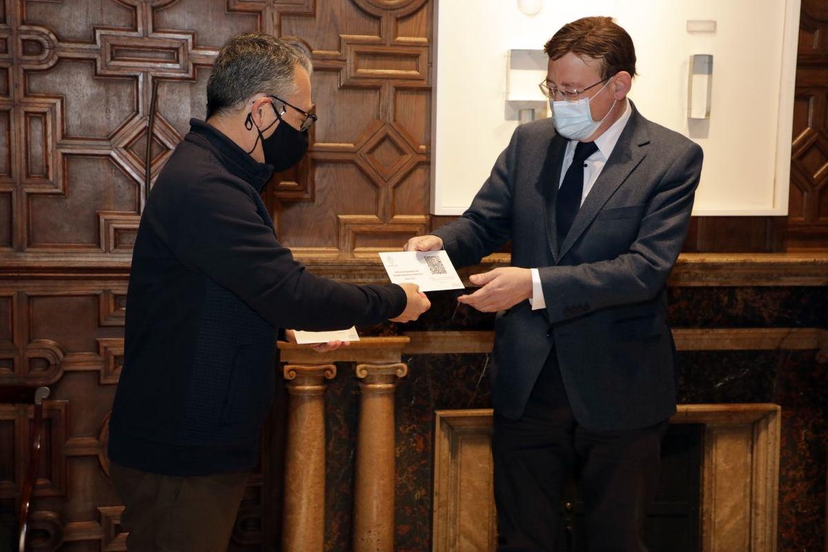el síndico mayor, Vicent Cucarella, hace entrega del informe al presidente regional, Ximo Puig. (Foto: E. Mezquita).