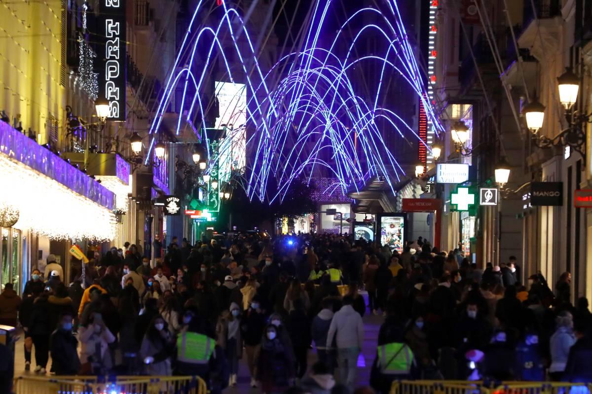 Personas se congregan para disfrutar de las luces navideñas en la calle de Preciados, el martes 8 de diciembre en Madrid (EFE/Ballesteros)