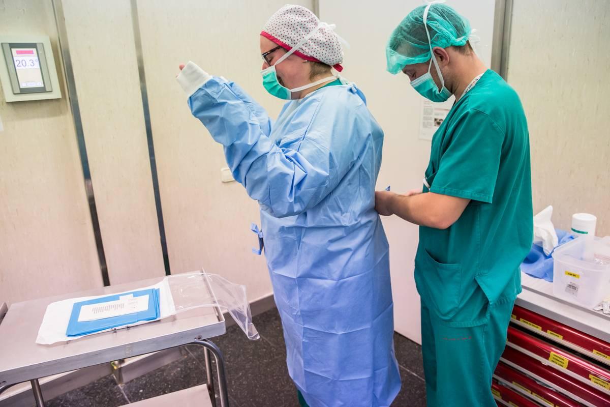Enfermera vestida por un compañero con la vestimenta quirúrgica en la Unidad de Cirurgía Ambulatoria (UCA) del Hospital Sant Joan de Déu de Barcelona. (Foto: Ariadna Creus i Àngel García)