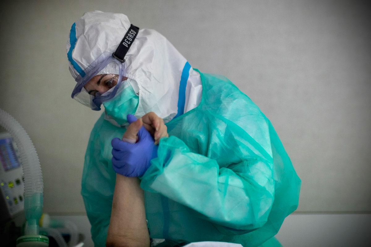 Un sanitario atiende a un paciente de covid en el Hospital Infanta Sofía. Foto: Alberto di Lolli