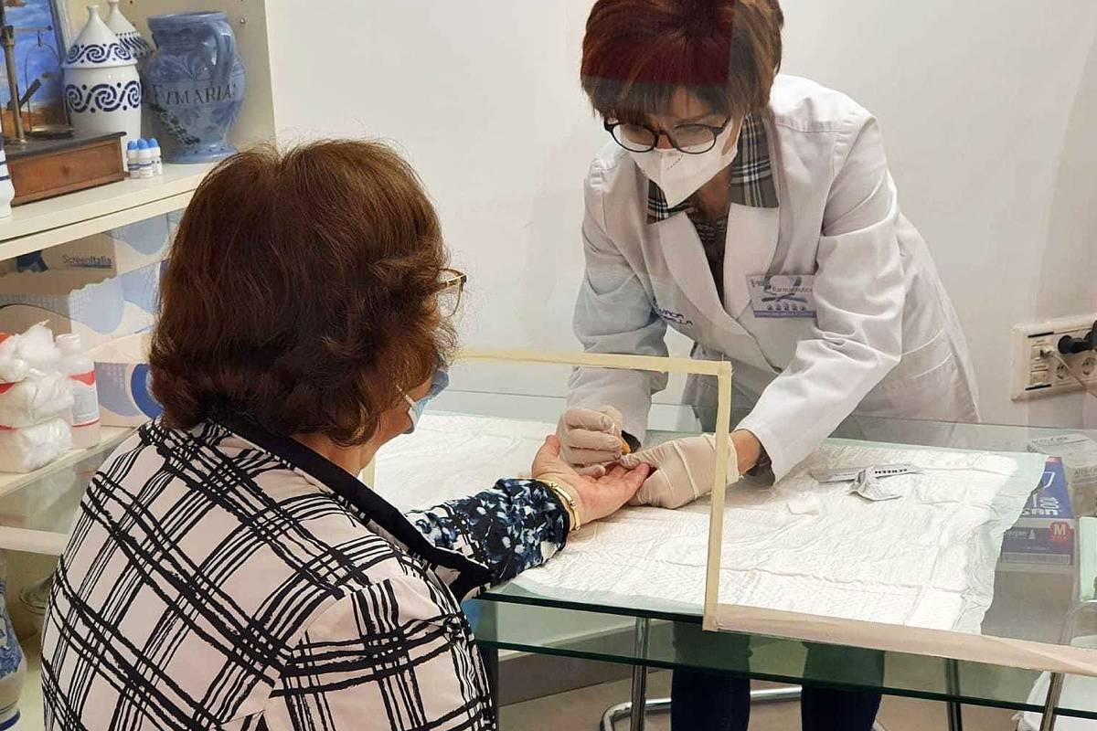 na farmacéutica de Orense realiza un test rápido de anticuerpos (punción dactilar) a una paciente en su botica.