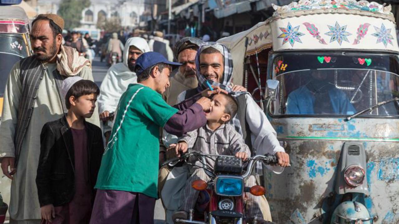 Abdhul Rahman, voluntario de vacunación contra la poliomielitis, administra la vacuna oral a un niño afgano.
