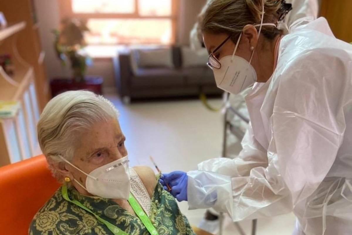 Una residente del centro DomusVi de Alcalá de Henares recibe la vacuna contra la covid-19.