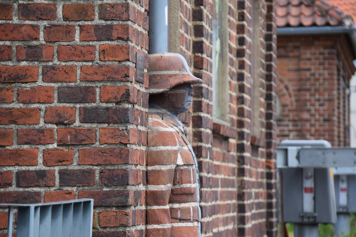 Una estatua camuflada en los ladrillos de un edificio.