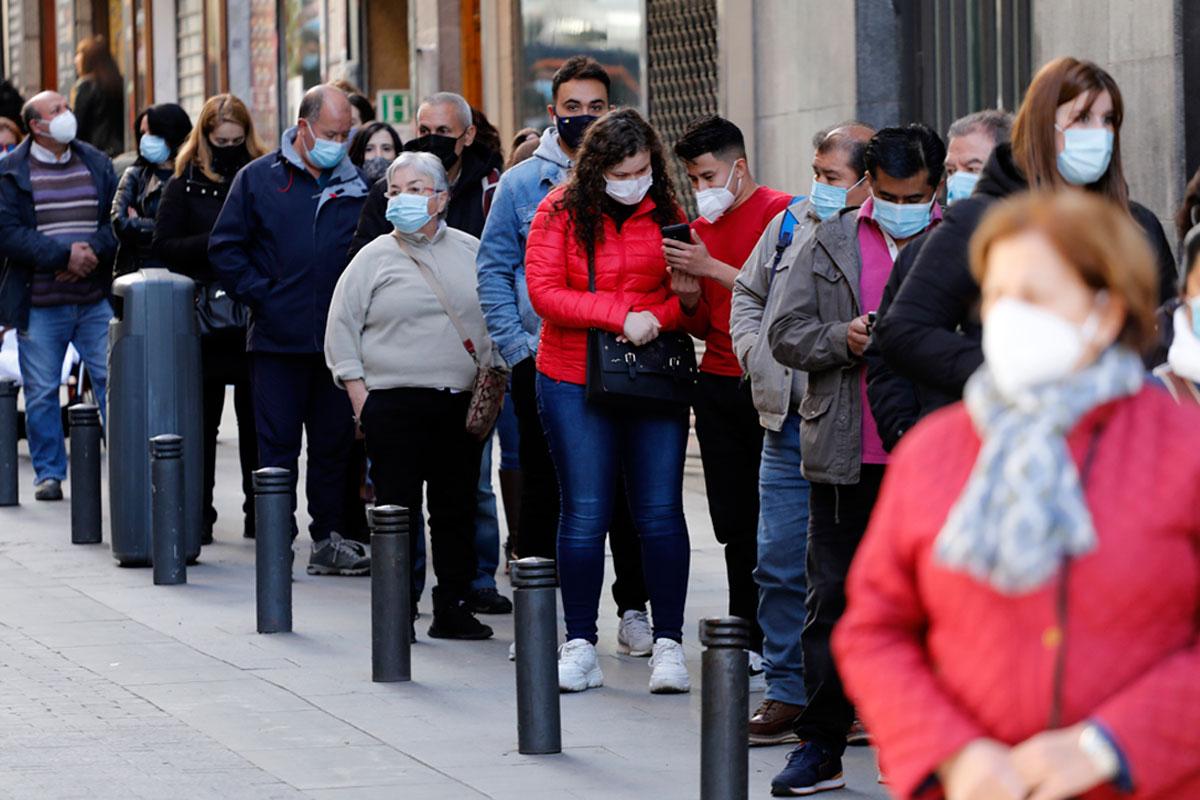 Personas con mascarillas haciendo cola en una calle de Madrid