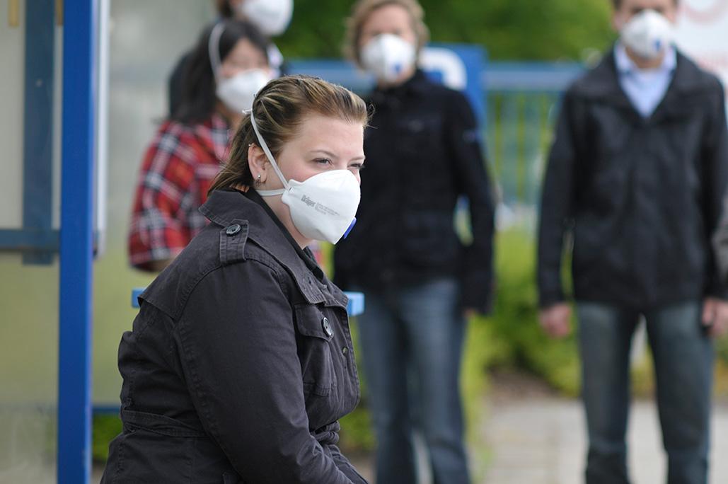 Mujer con mascarilla espera el autobús