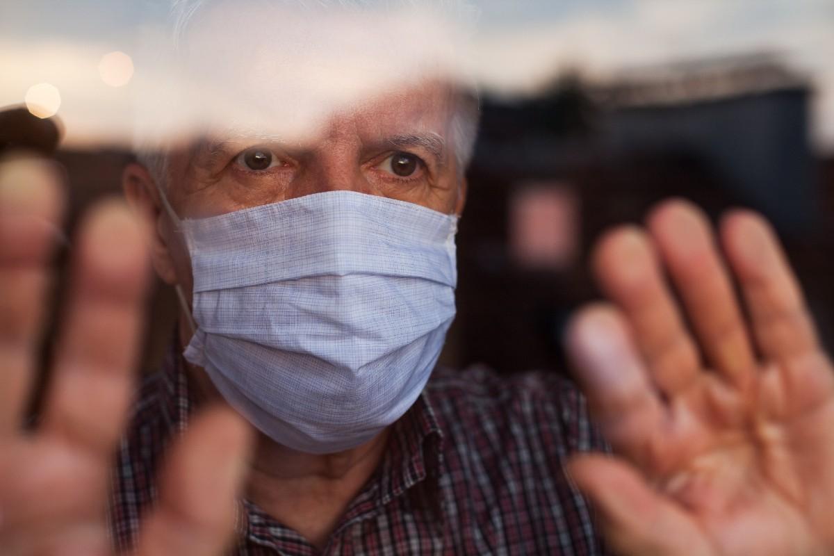 Anciano con mascarilla detrás de una ventana.
