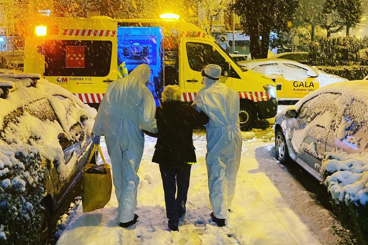 Dos sanitarios de Emergencias 112 ayudan a una señora a caminar sobre la nieve (FOTO: CAM).