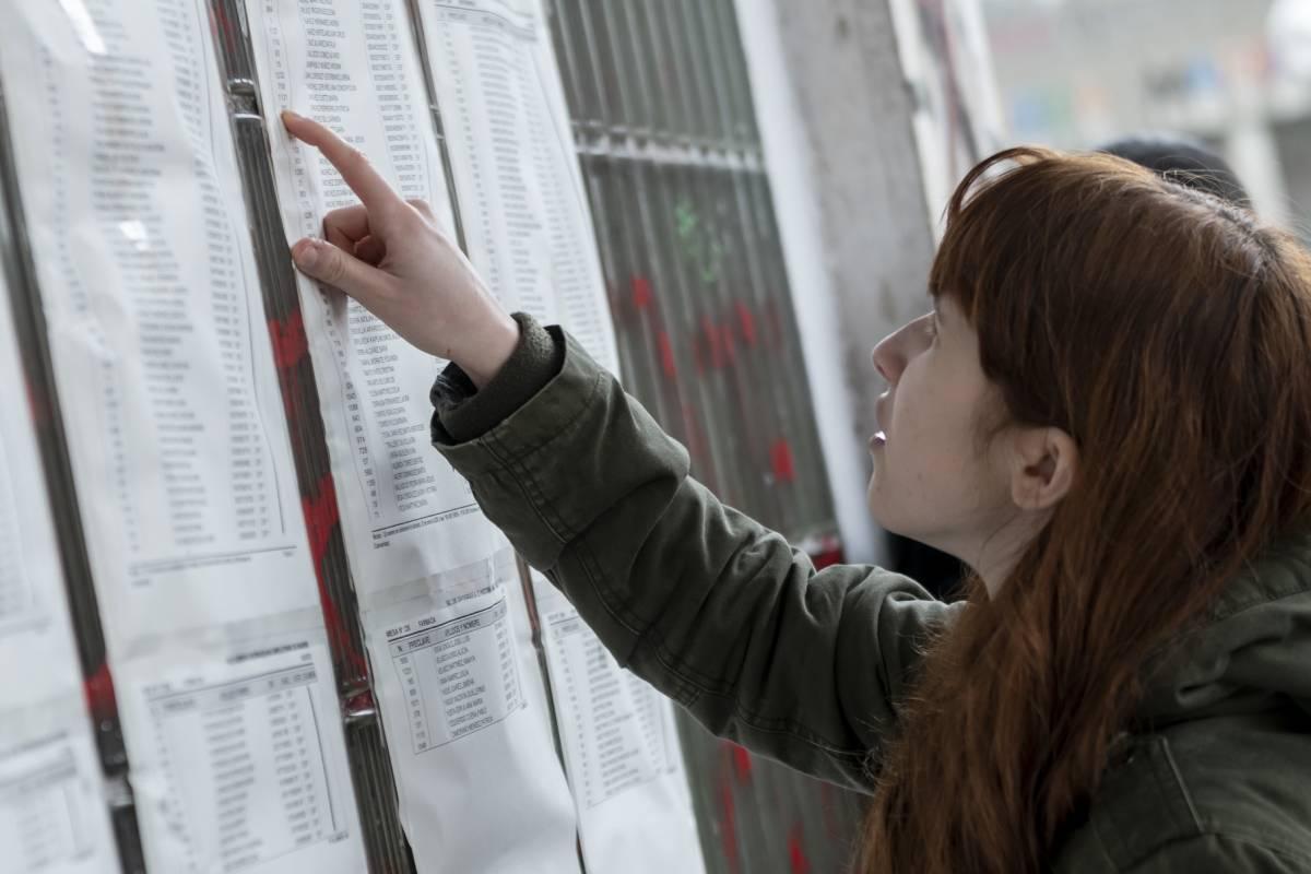 Aspirante mirando los listados de las aulas de los exámenes de FIR y EIR 2020 (José Luis Pindado)