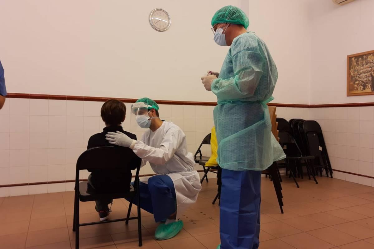 Un enfermero escolares realizando una PCR a un niño en un colegio.