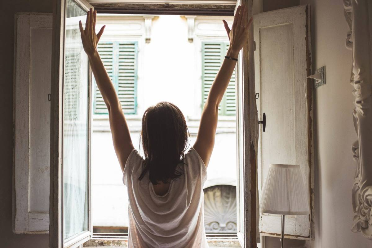 Mujer estirándose frente a una ventana.