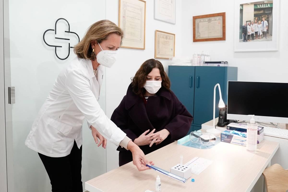 La presidenta de la Comunidad de Madrid, Isabel Díaz Ayuso, con la farmacéutica Pilar Varela, en su farmacia.