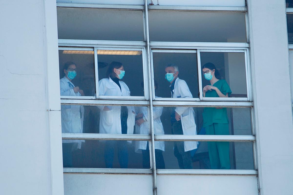 Profesionales sanitarios al lado de la ventana de un hospital.