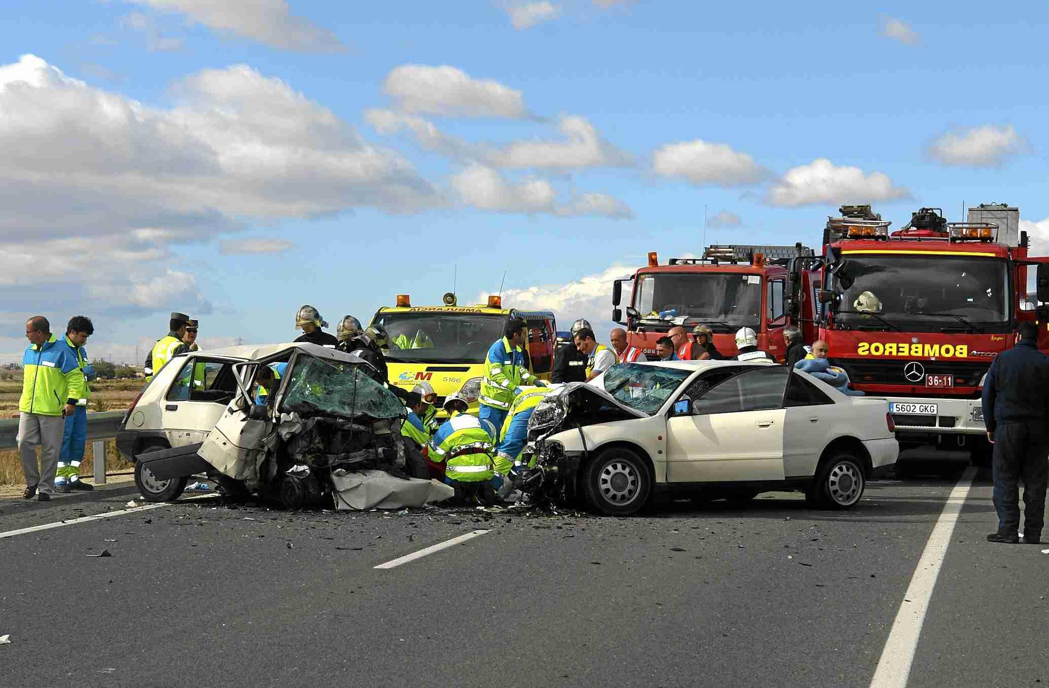 Dos coches en un accidente de tráfico, con ambulancias, personal médico y bomberos.