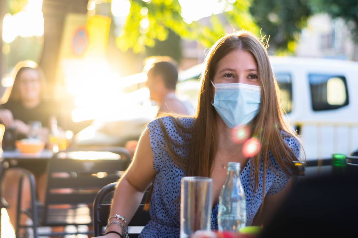 Mujer con mascarilla en una terraza de bar