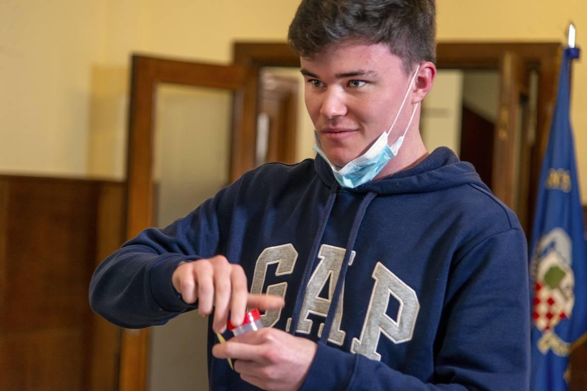 Un estudiante de la Universidad Complutense abriendo el bote para una automuestra de saliva. /UCM.