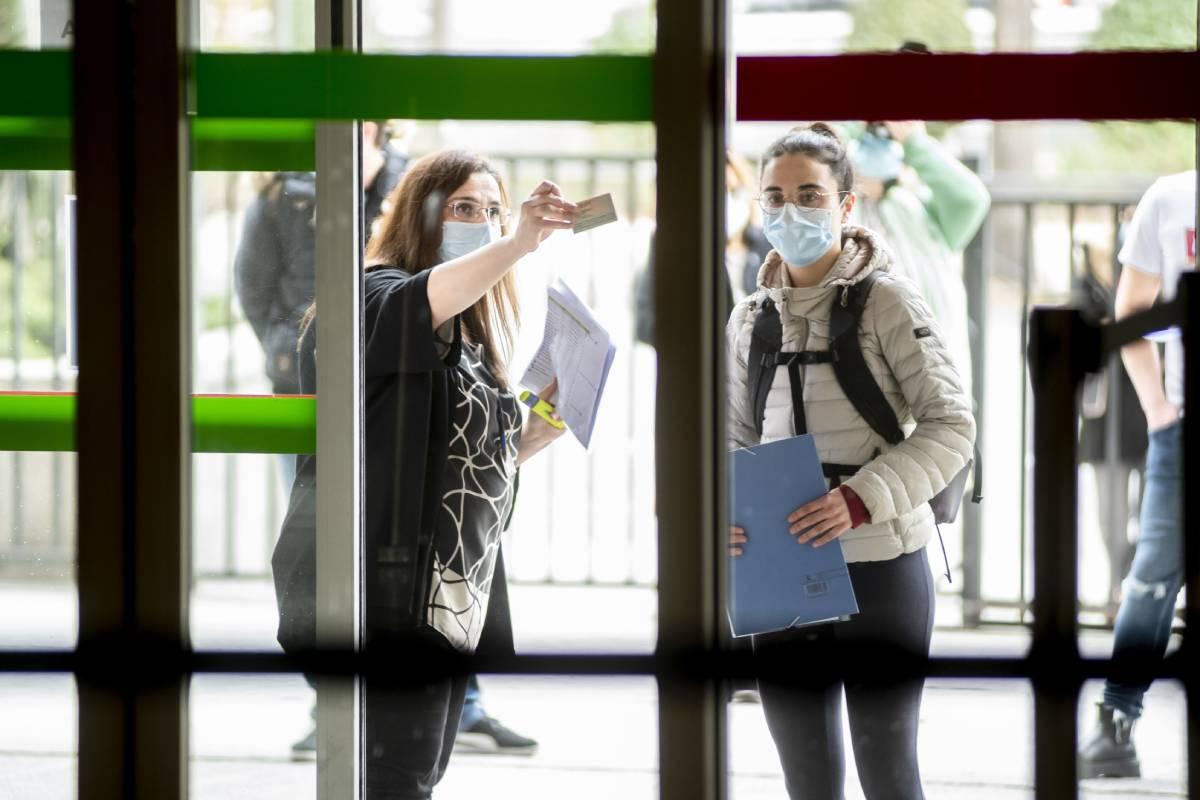 Una funcionaria comprueba la identidad de una de las aspirantes antes de entrar al Ministerio de Sanidad para hacer el examen MIR 2021 (José Luis Pindado)