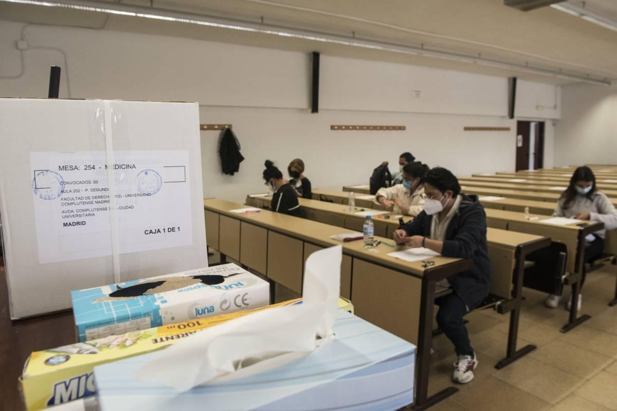 Los aspirantes se sientan en un aula de la Universidad Complutense de Madrid, a la espera de que les repartan el examen MIR 2021 (Foto: Luis Camacho).