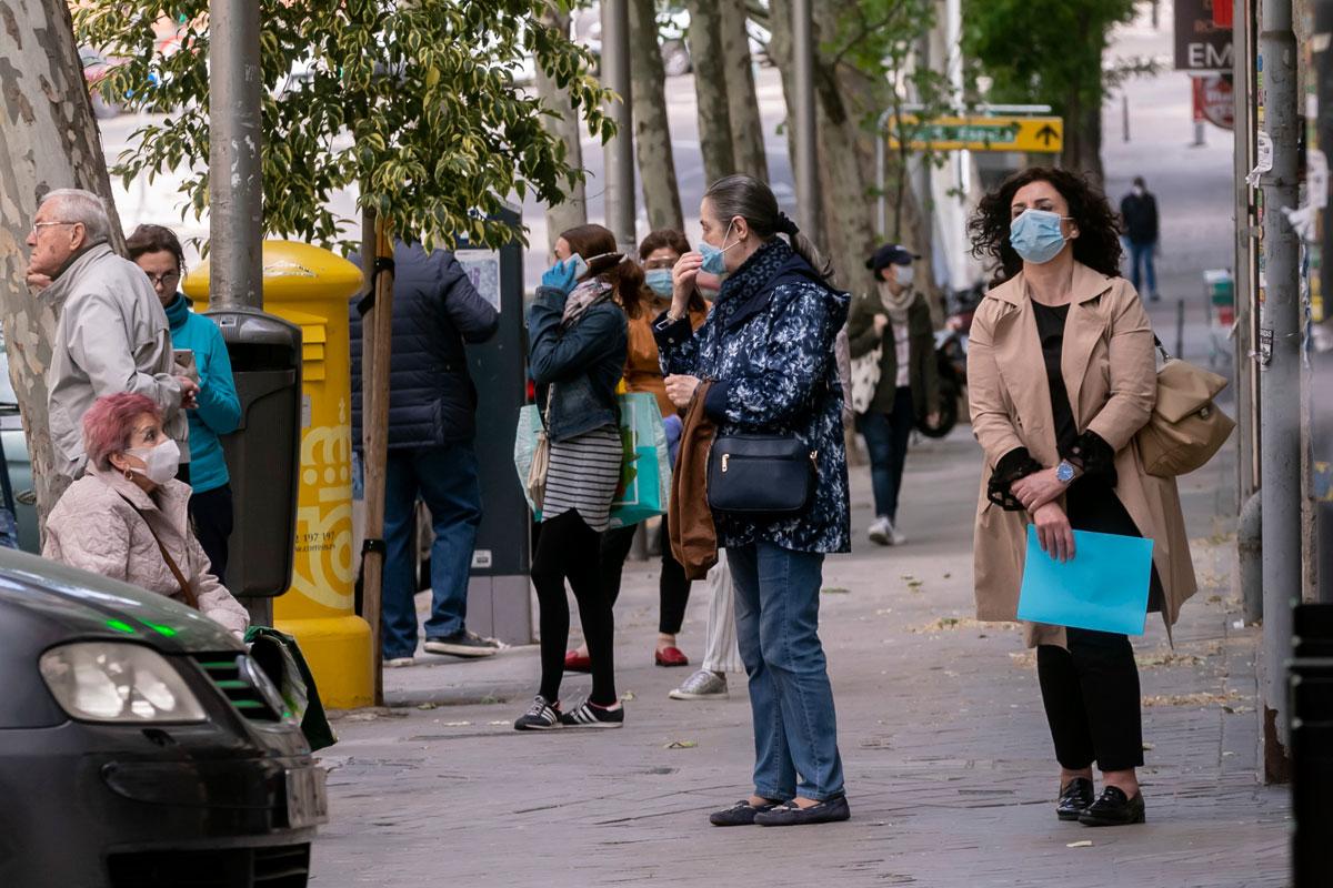 Gente pasea con mascarilla en una calle de Madrid.