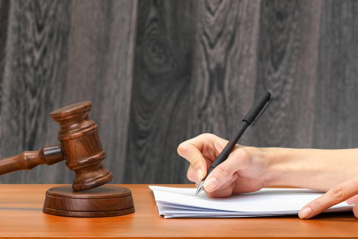 Juez realizando la firma de una sentencia.