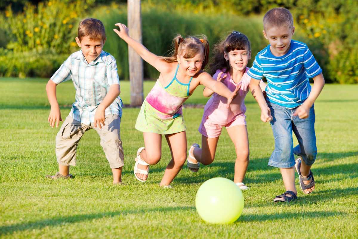 Niños jugando a la pelota en un parque.