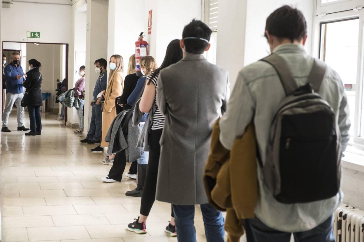 Aspirantes de formación sanitaria especializada en uno de los pasillos de la Facultad de Derecho de la UCM, esperando a entrar