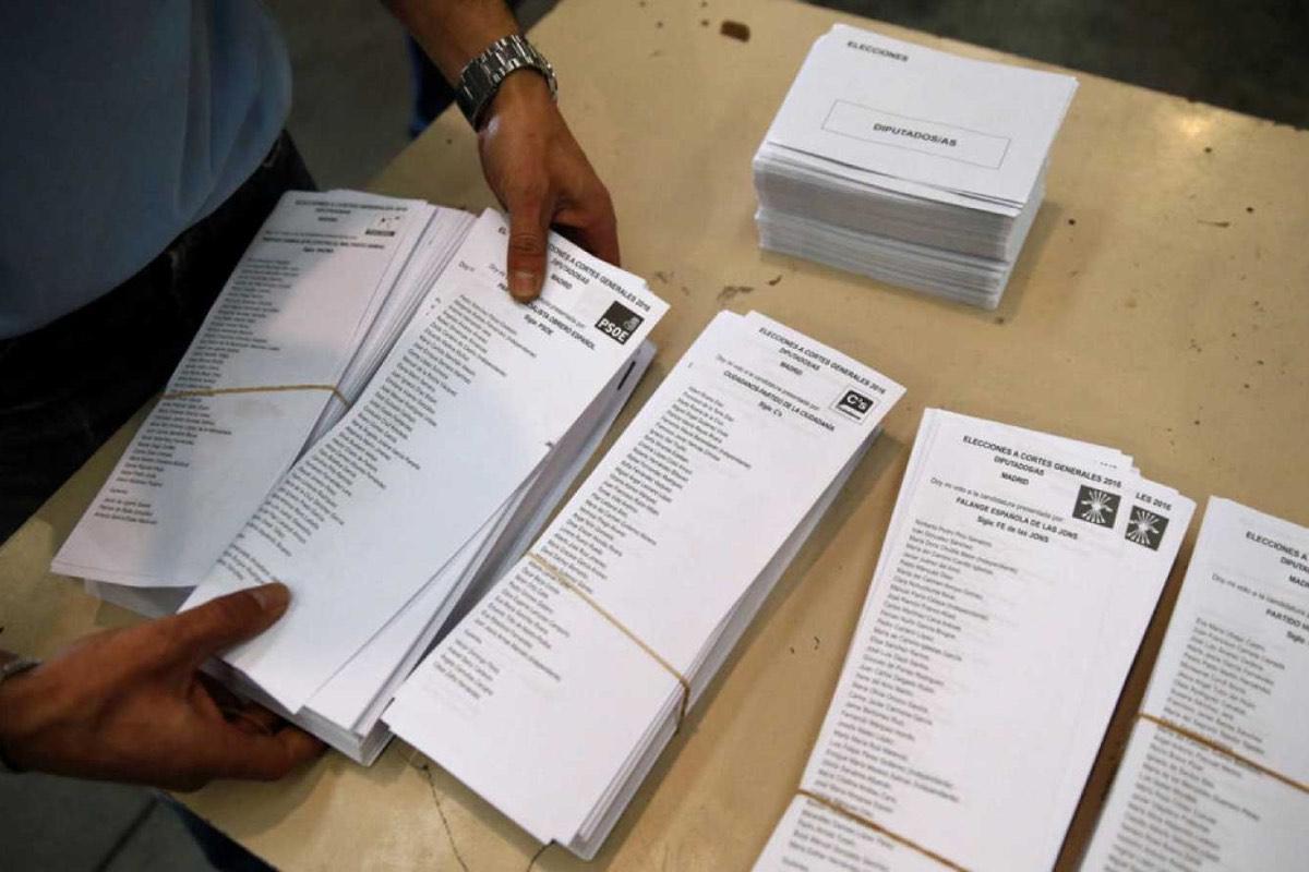 Un interventor distribuye papeletas de voto en una mesa electoral
