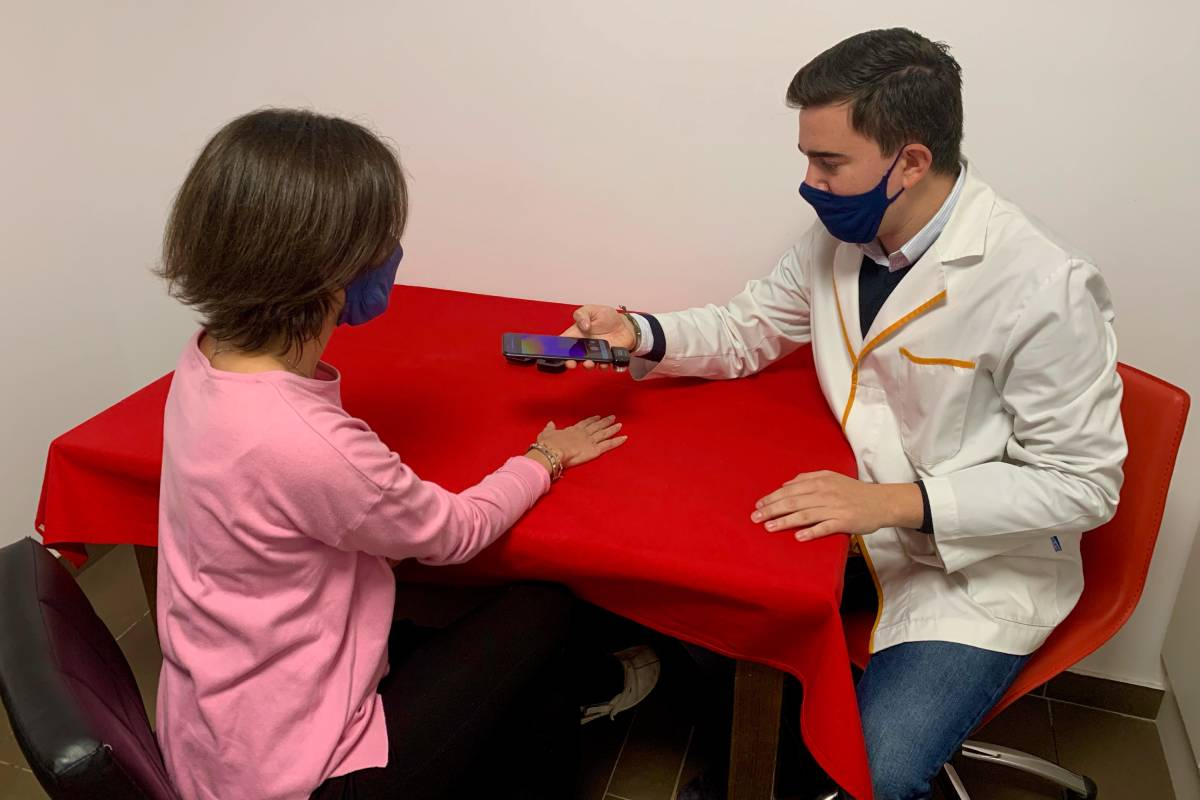 El farmacéutico Genar Esteve aplica 'RheumaTest' en una paciente en la Farmacia Esteve, en Igualada.