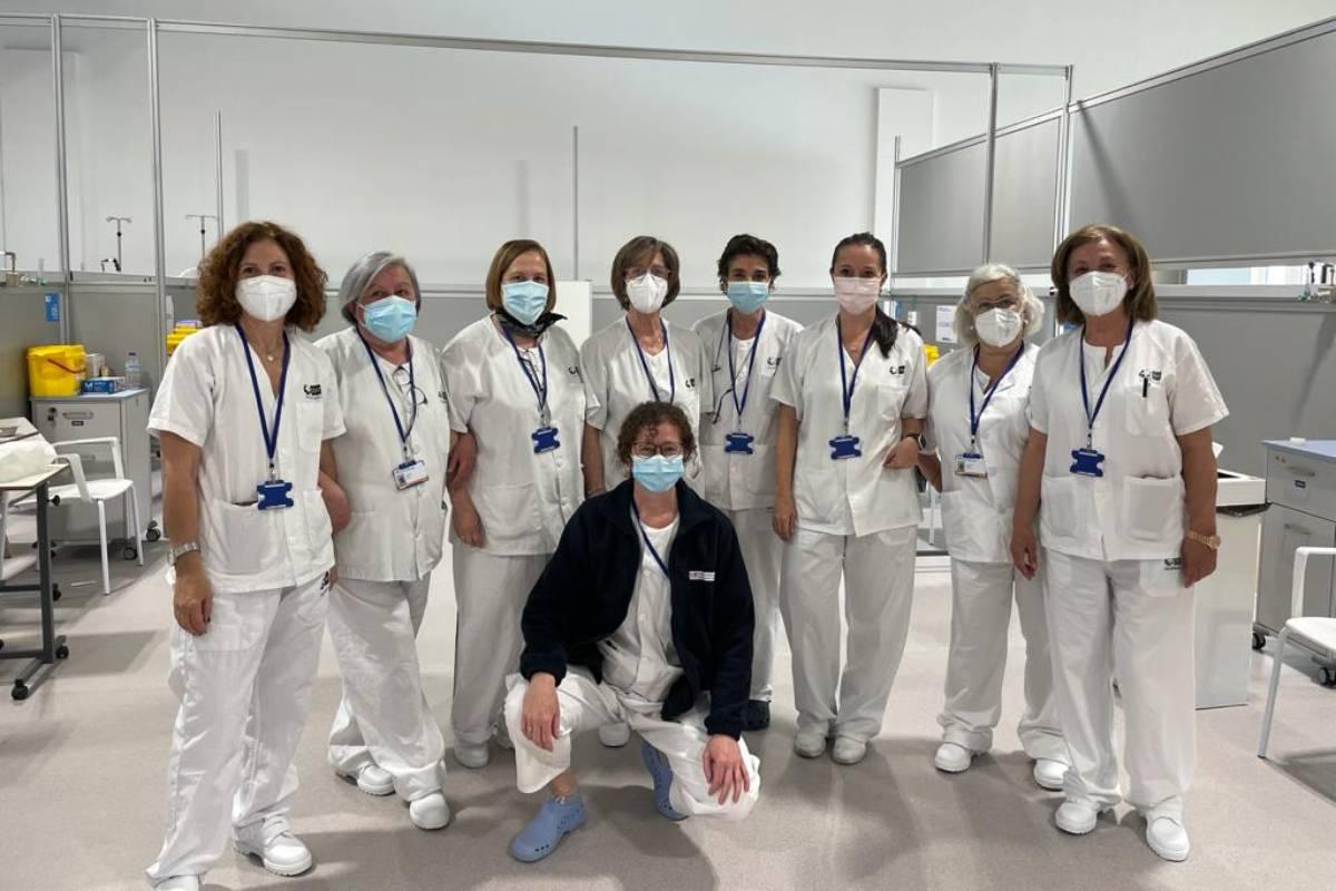 Siete de las 28 enfermeras jubiladas voluntarias que han comenzado hoy a vacunar en el Hospital Isabel Zendal posan junto a Verónica Real Martínez, directora de Enfermería (mascarilla rosa), y Eva González, supervisora de mañana de vacunación (con chaqueta azul).