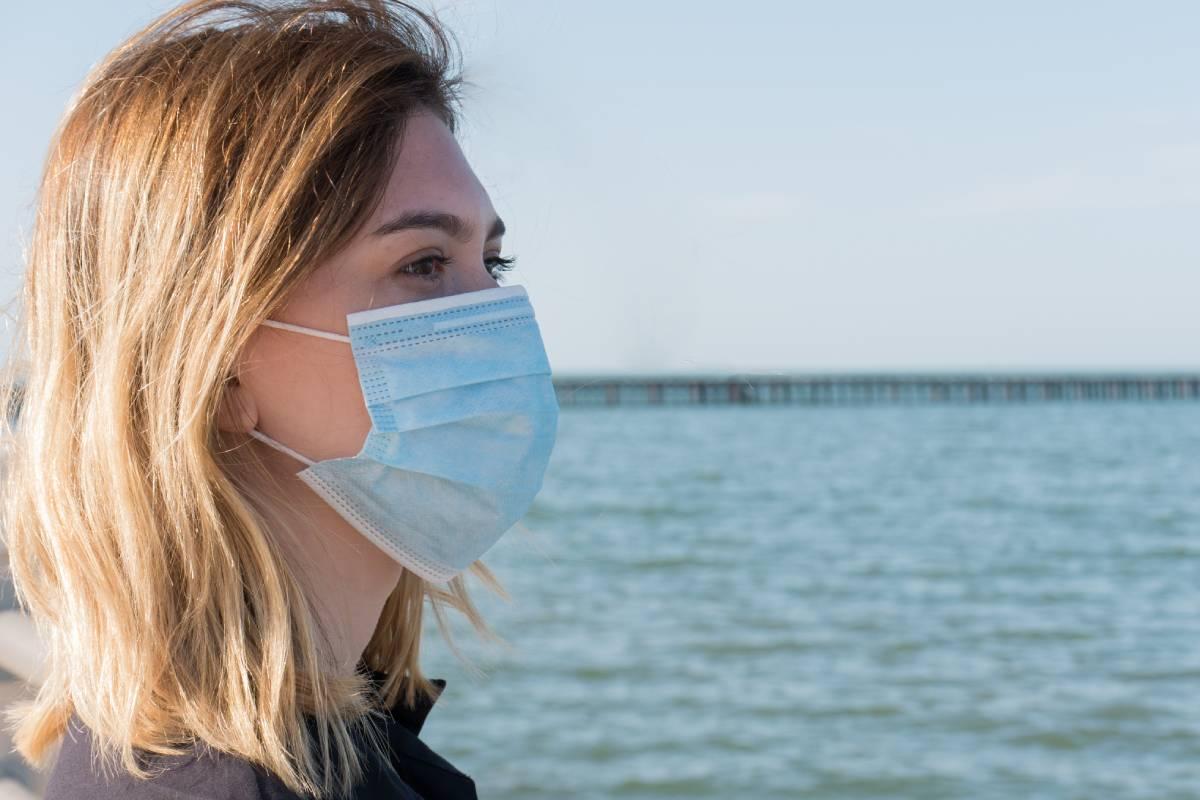 Una mujer con mascarilla, disfrutando del aire puro.