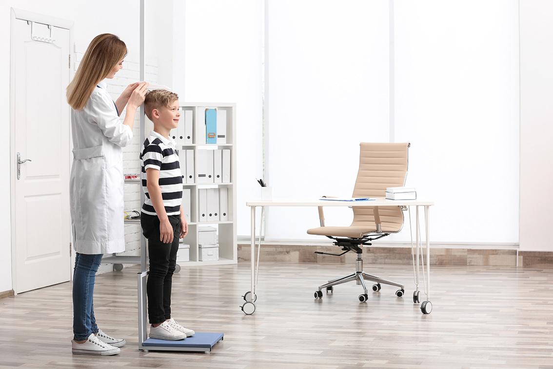 Doctora midiendo altura a niño en consulta.