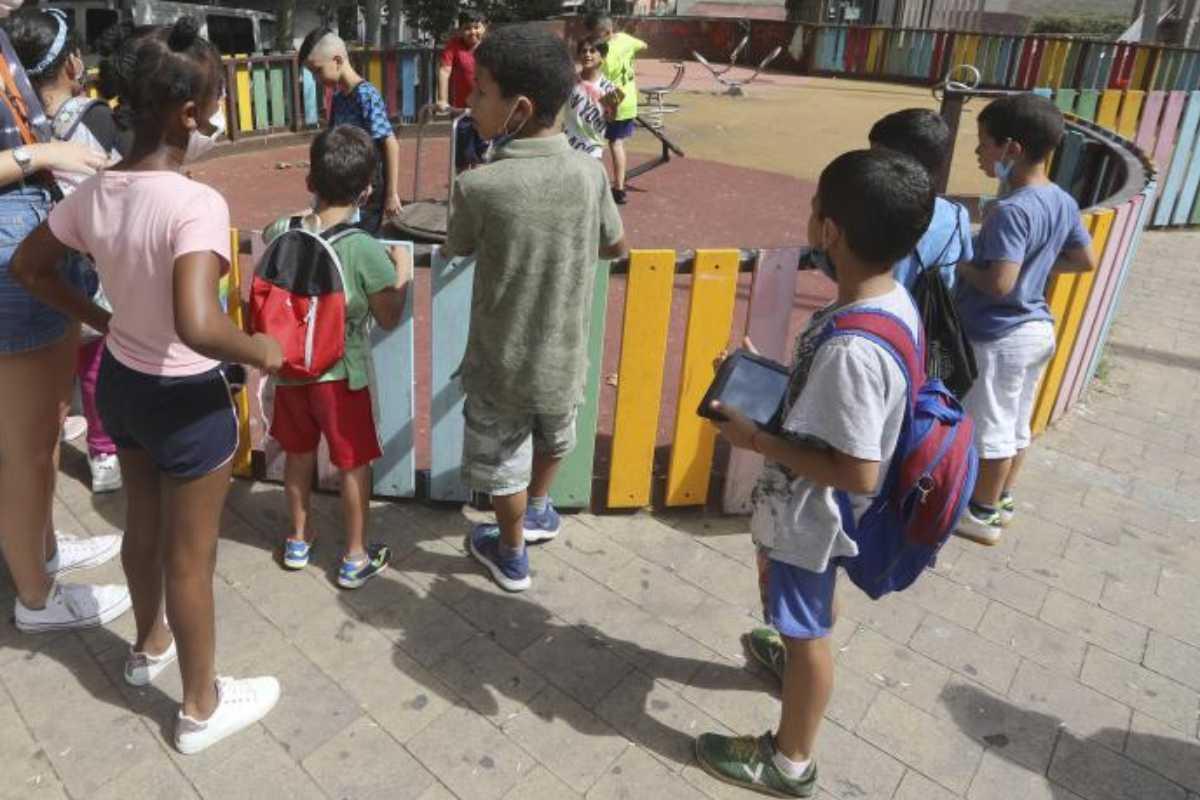 Niños con mascarillas en el parque, a la salida de la escuela.