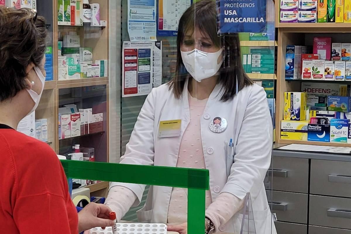 Una usuaria depositando una automuestra de saliva en una farmacia de Agolada (Pontevedra).
