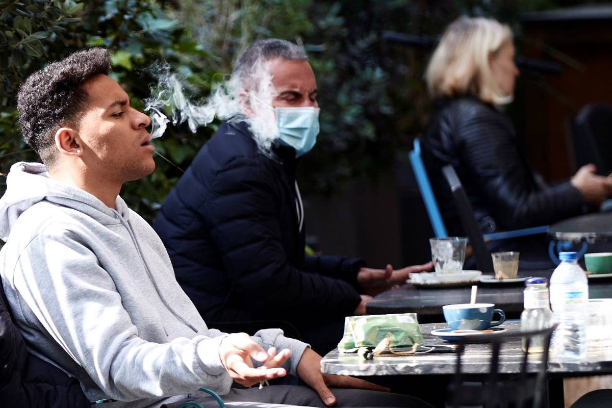 Un joven se quita la mascarilla para fumar en una terraza de Cataluña (Foto: EFE/Alejandro García)