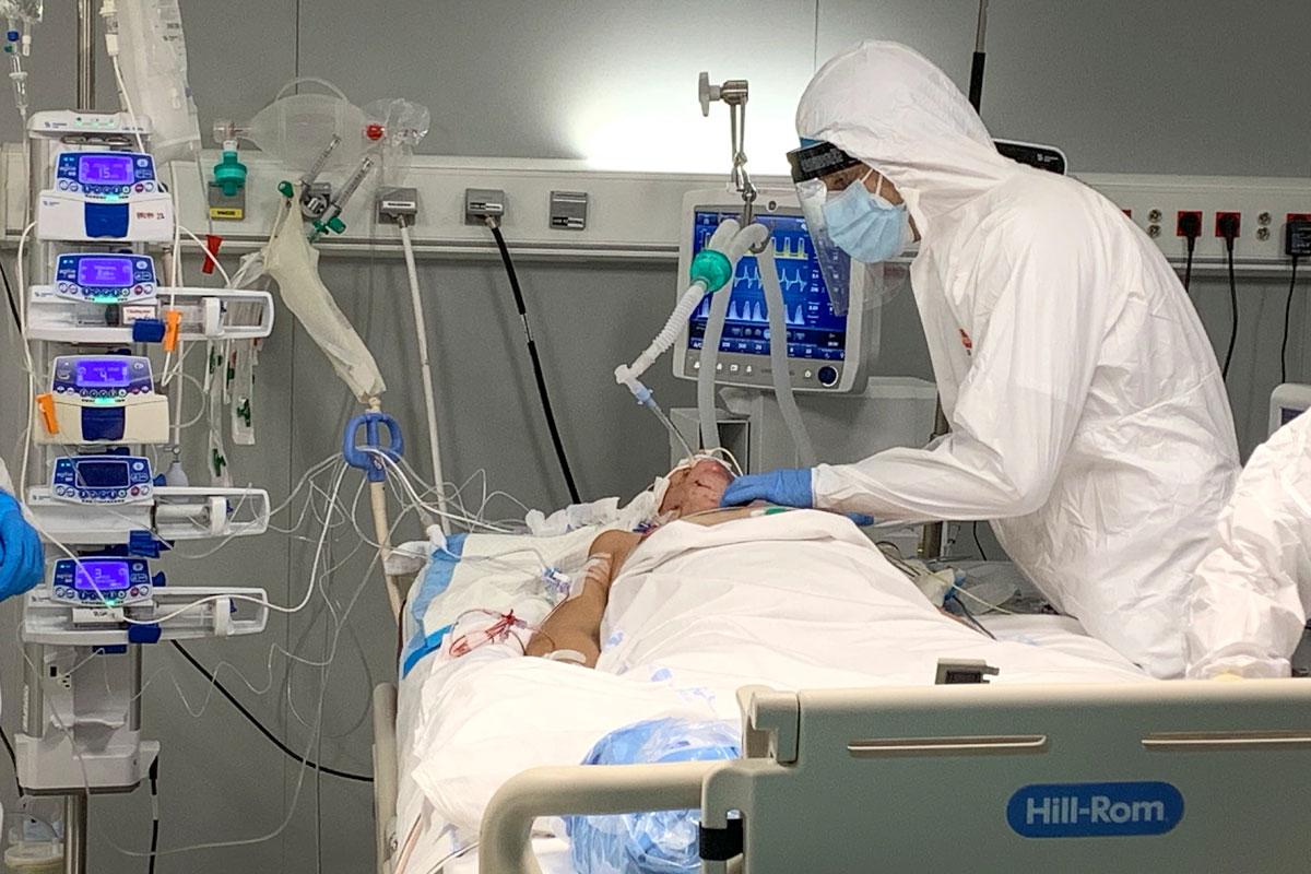 Un sanitario atiende a un paciente en la UCI del Hospital Enfermera Isabel Zendal