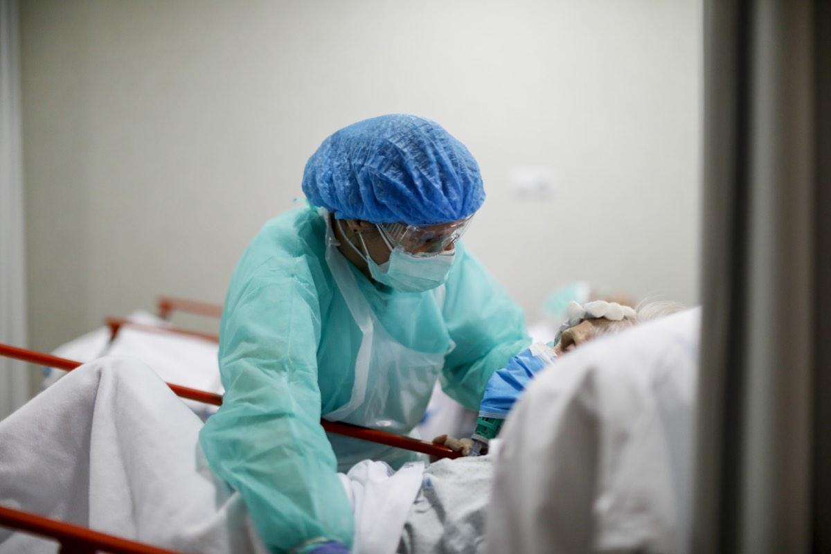 Una doctora reconforta a un paciente aquejado de coronavirus en el Servicio de Urgencias de un hospital de Madrid (FOTO: Alberto Di Lolli).