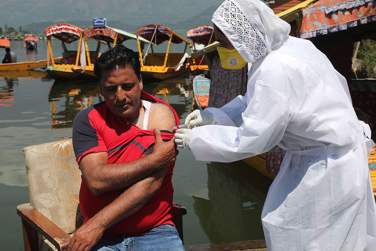 Un hombre es vacunado en India.