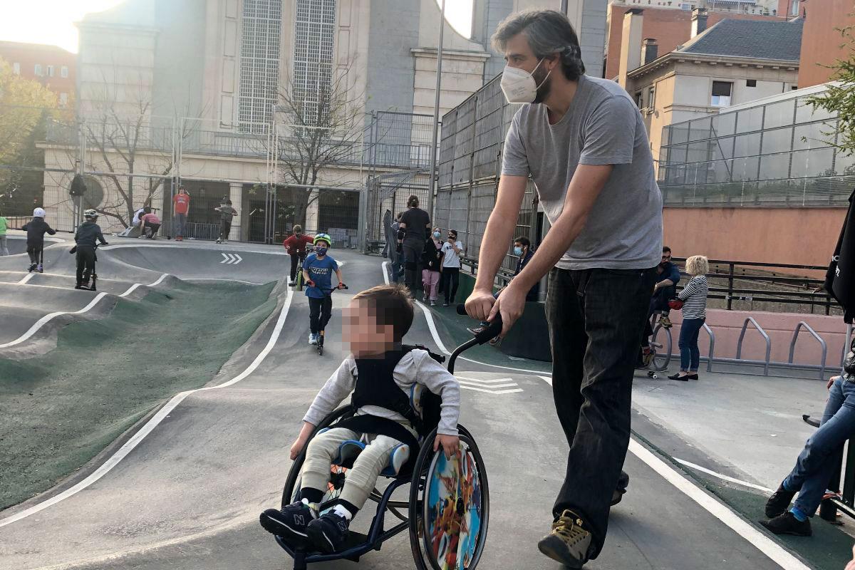 Un niño en silla ruedas paseado por su padre.