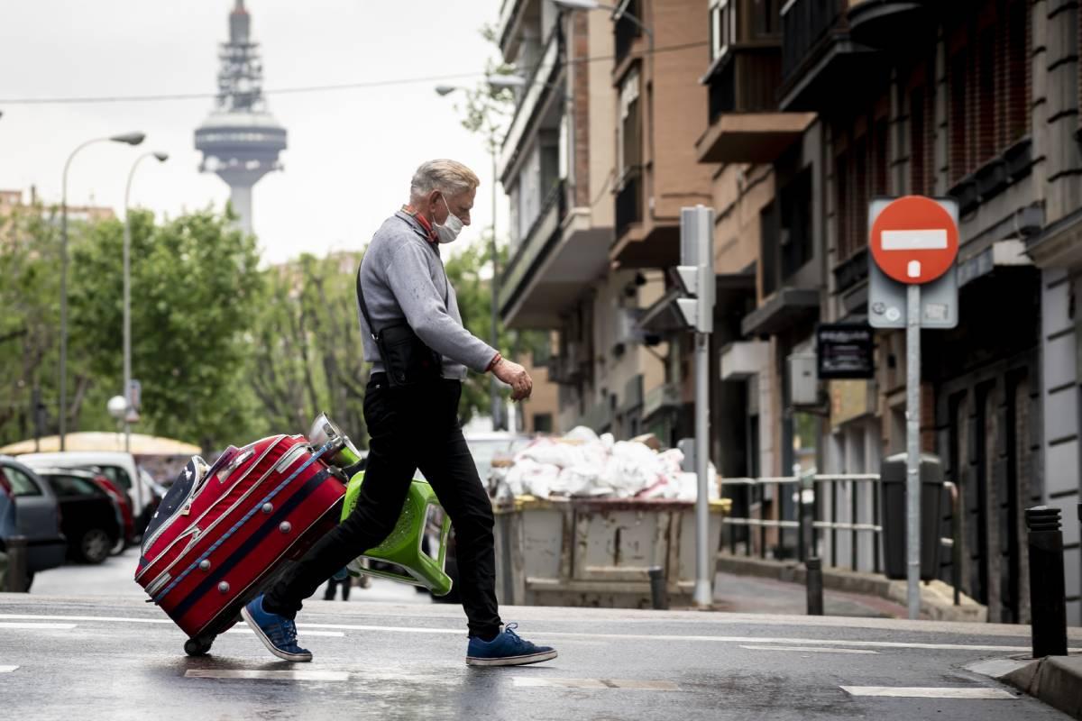 Un transeúnte con mascarilla y maleta en Madrid. /JL. Pindado.