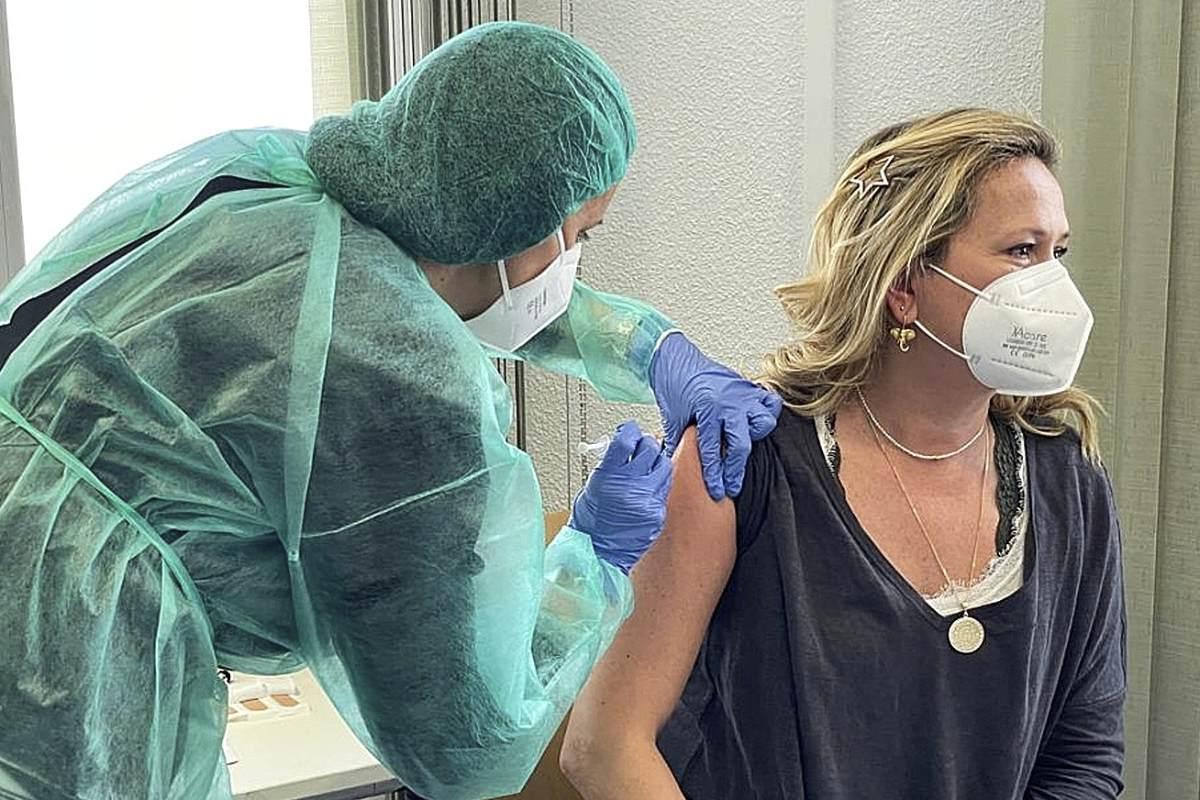 Una farmacéutica vacunando en el COF de Madrid a una compañera que realiza test de ant�genos en una farmacia.