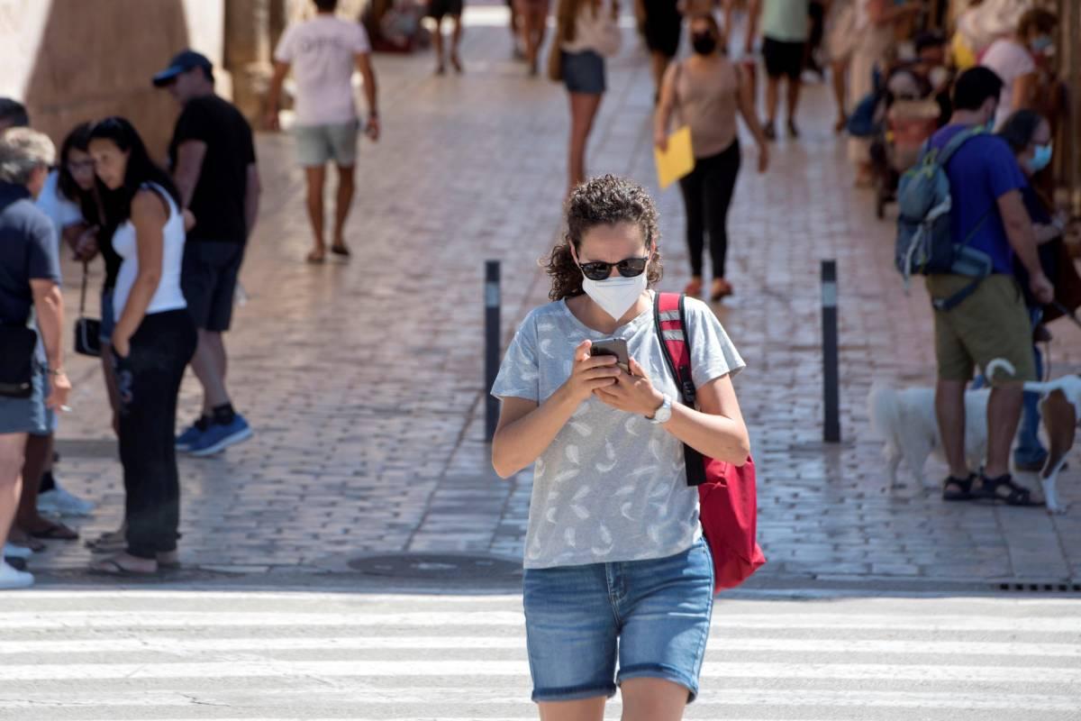 Una mujer cruza un paso de peatones en el casco histórico de Ciutadella, Menorca.  (EFE/ David Arquimbau Sintes)
