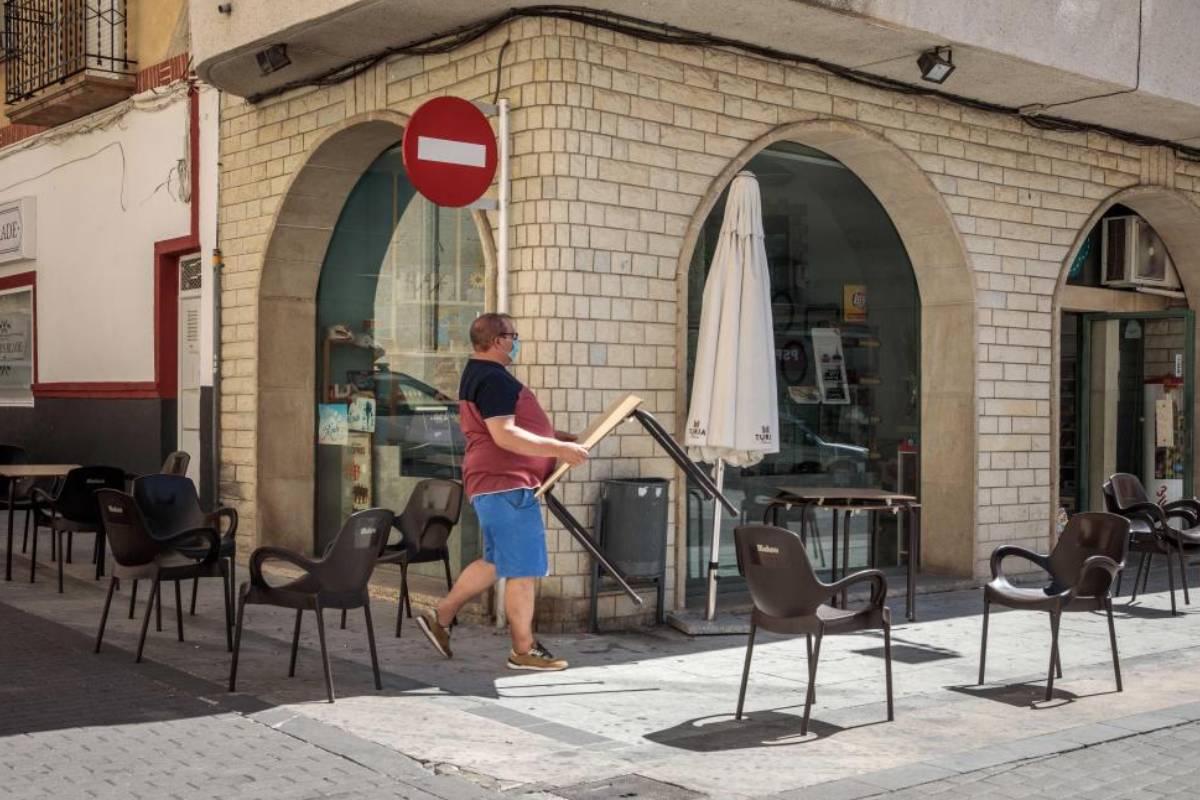 Un hombre recoge las mesas de su terraza en un establecimiento de la Comunidad Valenciana.