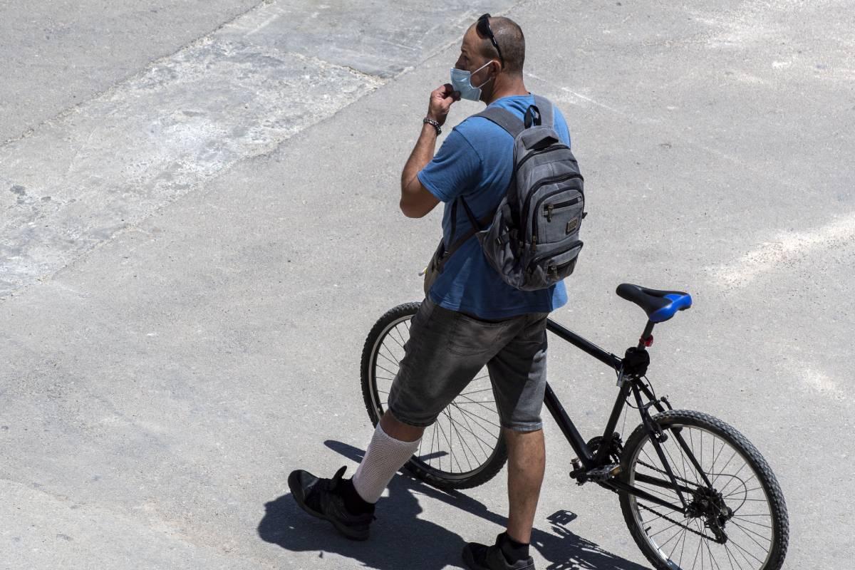 Un ciclista con su bicicleta y su mascarilla por el centro de Palma de Mallorca el sábado 26 de junio. /EFE (Cati Cladera).